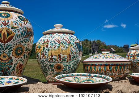 Colorful ceramic handmade tableware on a blue sky background