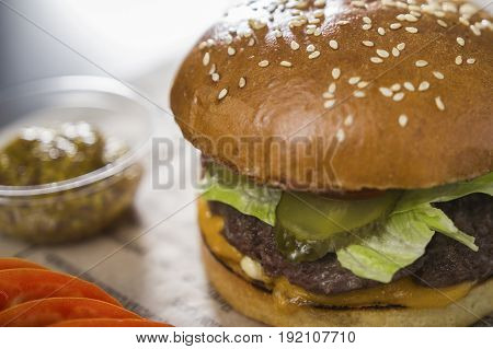 Big tasty burger with mustard on the table, in a cafe