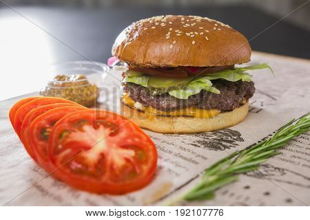 A large tasty burger with sliced tomato on a table, in a cafe