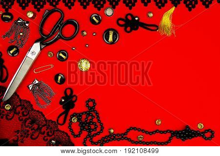 Sewing kit isolated on red background: scissors pins accessories buttons metal buckles black lace and necklace