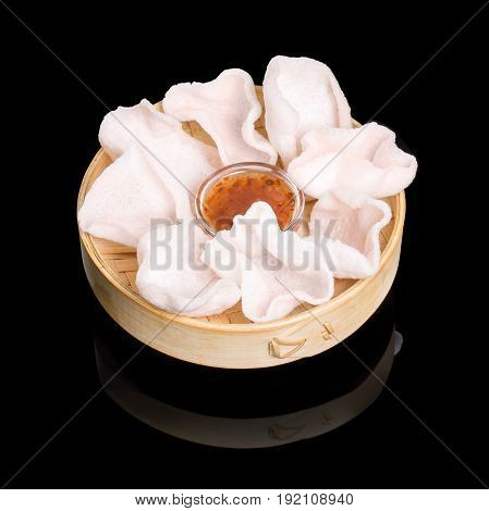 Rice crisps with sauce to basket. On a black background with reflection