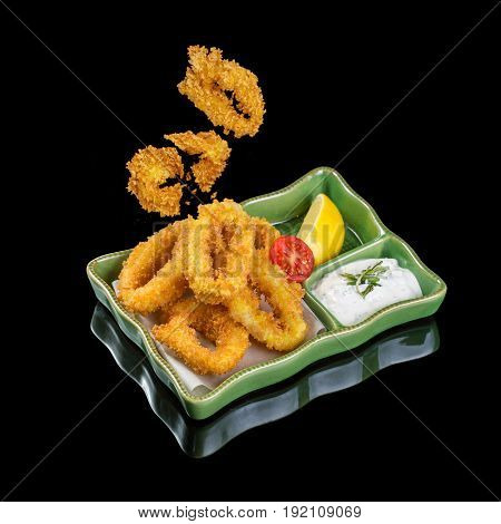 Fried squid rings on a plate. Black background with reflection. Flying