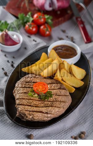 Beef steak in a frying pan with a garnish of potatoes.