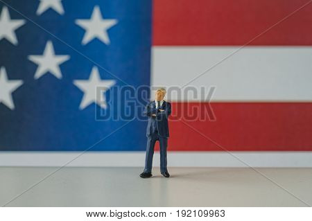 Independence day celebration with miniature american businessman standing on wood floor in front of United State national flag in the background.
