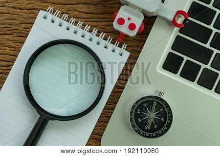 SEO search engine optimization concept with compass computer robot and magnifying glass on white note book on wood table.