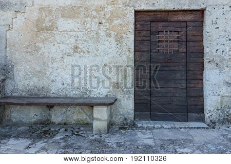 Aged vintage wooden door on stone building cave in Matera south Italy.