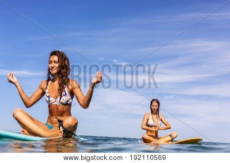 Two Beautiful Sporty Girls Surfing In The Ocean.