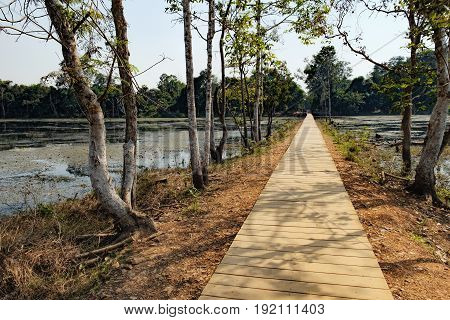 Mysterious wooden path towards Neak Pean Temple through artificial island in Angkor Complex, Siem Reap, Cambodia. Ancient Khmer architecture, famous Cambodian landmark, World Heritage