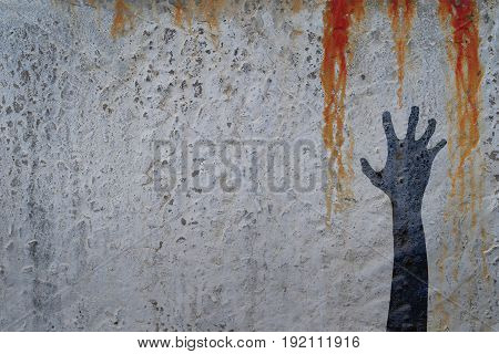 Zombie hand silhouette in shadow on concrete wall and blood background with copy space for text or image. Zombie and halloween theme illustration.