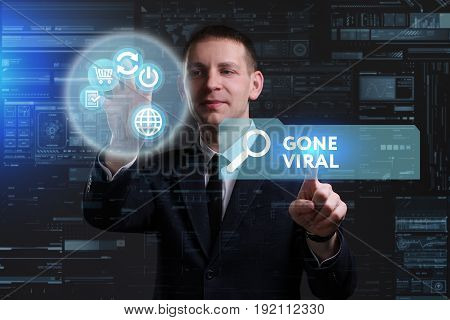 Business Technology Internet and network concept. Young businessman working on a virtual screen of the future and sees the inscription: Gone viral