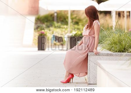 Fashionable clothing fashion and trends concept. Woman in long dress and red high heels standing on city street