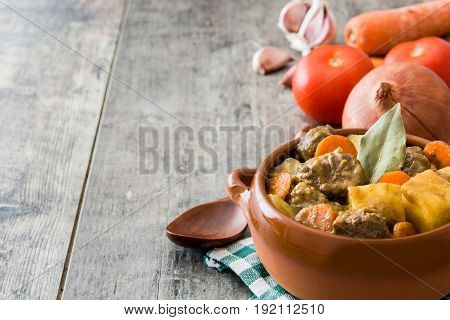 Beef meat stewed with potatoes, carrots and spices in ceramic bowl on wooden table
