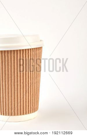 Cropped picture of paper mug. Cardboard cup of hot coffee.