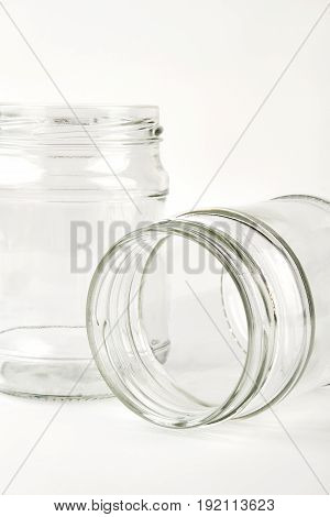 Closeup of two glass jars. Clean storage capacity, white background.