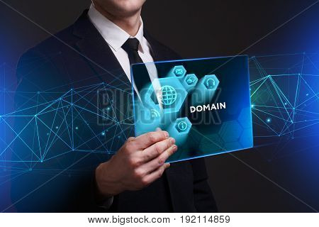 Business Technology Internet and network concept. Young businessman working on a virtual screen of the future and sees the inscription: Domain