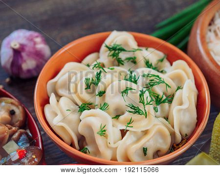 Closeup view of traditional russian food - pelmeni, ravioli or meat dumplings - on brown wooden table. Served with marinated mushrooms, sauerkraut, salted cucumbers, green onion and garlic. Copy space