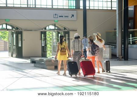 Group of young tourists at the station. In hands at girls suitcases tickets passports. Summer tourism. View from a back.