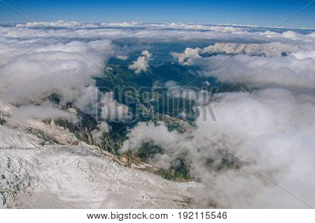 View of peaks, glacier and Chamonix Valley from the Aiguille du Midi, in French Alps Chamonix Mont Blanc, alpine mountains landscape, blue sky in sunny summer day