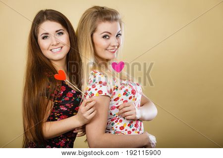 Two happy women holding heart on stick having fun wearing tshirts with flower pattern. Photo and carnival funny accessories concept.