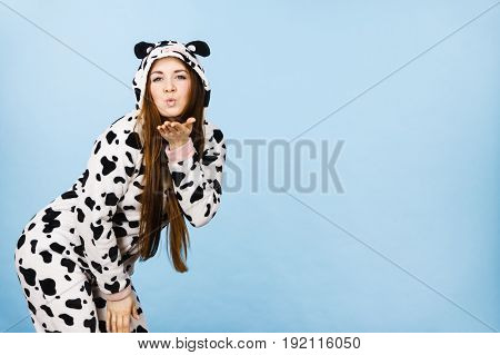 Happy teenage girl in funny nightclothes pajamas cartoon style sending kiss positive face expression studio shot on blue.