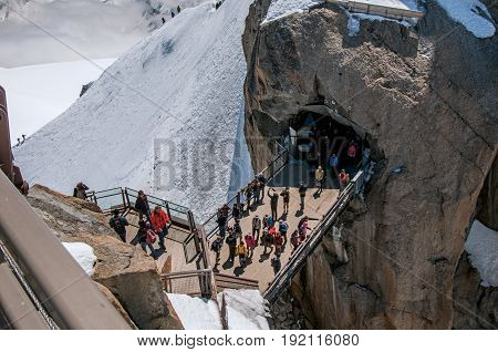 Footbridge with tourists on the Aiguille du Midi, in French Alps Chamonix Mont Blanc, alpine mountains landscape, clear blue sky in warm sunny summer day