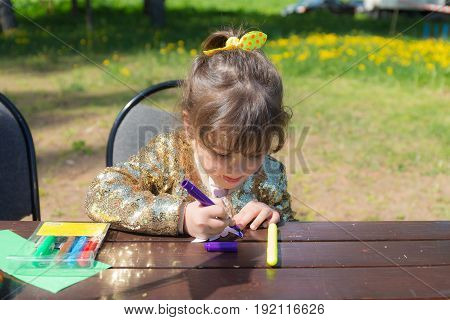 Little girl at the table draws colored markers