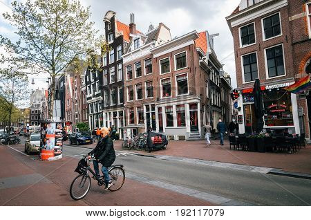 Amsterdam Netherlands - 25 April 2017: Adult woman rides a bicycle in red light district where prostitutes try to lure customers from windows. Typical architecture of Amsterdam