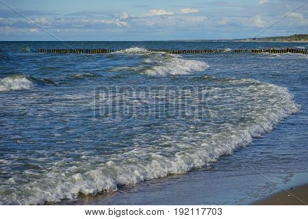 long and low waves of the Baltic sea are rolled on a sandy beach shoreline