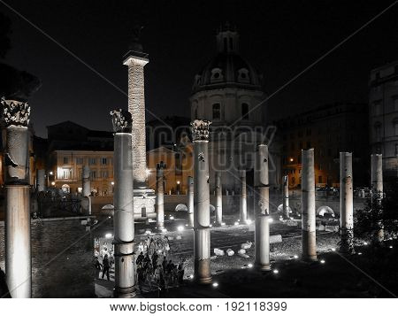ROME ITALY - JUNE 2 2017: Black and color photo with Trajan column church of Santa Maria di Loreto and ruins of Trajan forum at night.