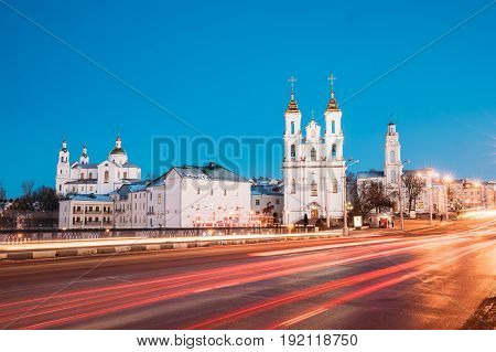 Vitebsk, Belarus - February 15, 2017: Traffic At Lenina Street And Landmarks On Background. Holy Assumption Cathedral, Holy Resurrection Church And City Hall In Evening Or Night Illumination At Winter