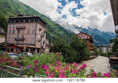 Chamonix, France - June 26, 2016. View of building, creek, flowers and the Mont Blanc in Chamonix, a famous ski resort located in Haute-Savoie Province, at the foot of Mont Blanc in the French Alps