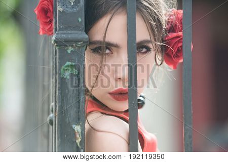 Girl With Rose In Hair At Iron Fence