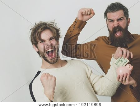 men with beards or friends laughing and putting money dollars in piggy bank with winner gestures on grey background. Savings budget finance cash and moneybox