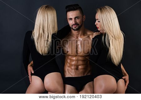 love relations. athletic man with muscular wet body and strong torso with sexy blonde girls in underwear pants and bodysuit on black background lesbian and gay homosexual seduction and foreplay