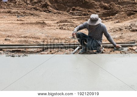 Man Pressing An Cement Tile Into A Glue On A Floor.
