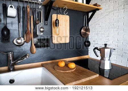 Design of a modern home kitchen in the attic and rustic style. Black wall with shelves trays jars mugs sink. In the background a wall of white brick.