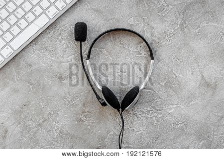 customer support service desktop with headset and keyboard on stone background top view