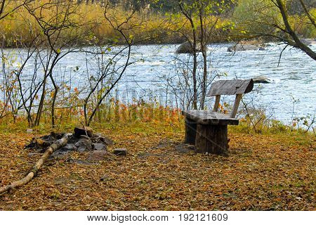 Wooden bench on the riverbank on autumn