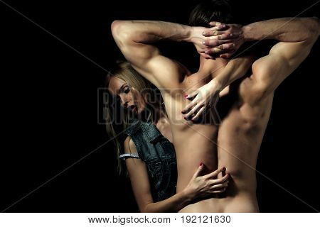girl or cute woman touching athletic man macho or bodybuilder with fit naked back torso and strong arms triceps biceps on black background. Couple in love. Desire and foreplay
