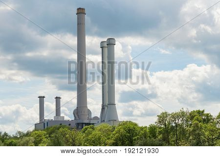 Industrial smokestack over green forest trees against clouds in sky