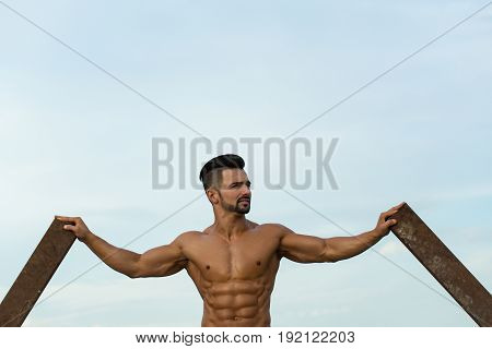 Guy With Muscular Body Training At Rusty Iron Rod