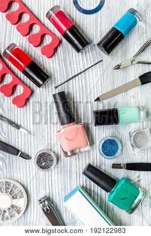 manicure preparation set with nail polish bottles on gray table background top view