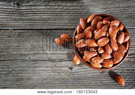 Tasty Almonds Nuts In Wooden Bowl On The Old Background With Place For Text. Top View. Copy Space.
