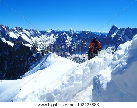 Two alpinists and mountaineer climber on AIGUILLE DU MIDI, CHAMONIX MONT BLANC french ALPS, top alpine mountains range landscape, FRANCE with clear blue sky in 2016 warm sunny summer day Europe on July.