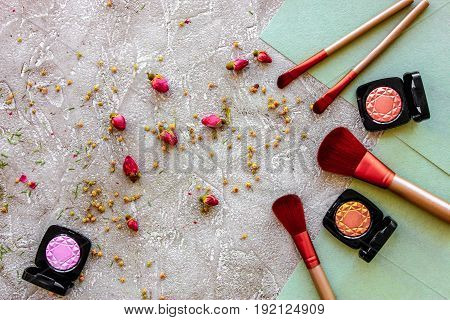 decorative cosmetics design with eye shadow and make-up brushes on gray table background top view pattern