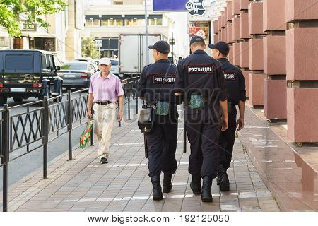 Three Police Patrol On A City Street On A Summer Day. Patch