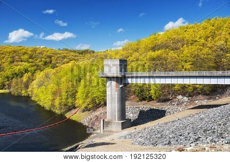 The lake side of Hop Brook Dam in Naugatuck connecticut on a sunny blue sky day.