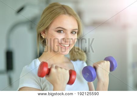 Sporty young woman training in gym lifting dumbbells