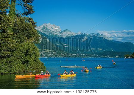 Annecy, France - June 28, 2016. Annecy lake with island, vegetation, kayaks, peaks and blue sky, in the historic Annecy, department of Haute-Savoie, Auvergne-Rhône-Alpes region, south-eastern France