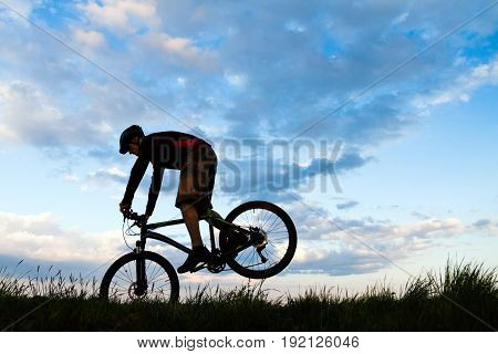 Mountain biker riding and jumping on bike in spring inspirational sunset silhouette. Man cycling MTB on enduro inspiring trail. Sport fitness motivation and inspiration.